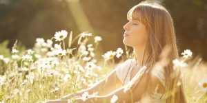 Woman with eyes closed sitting in meadow.